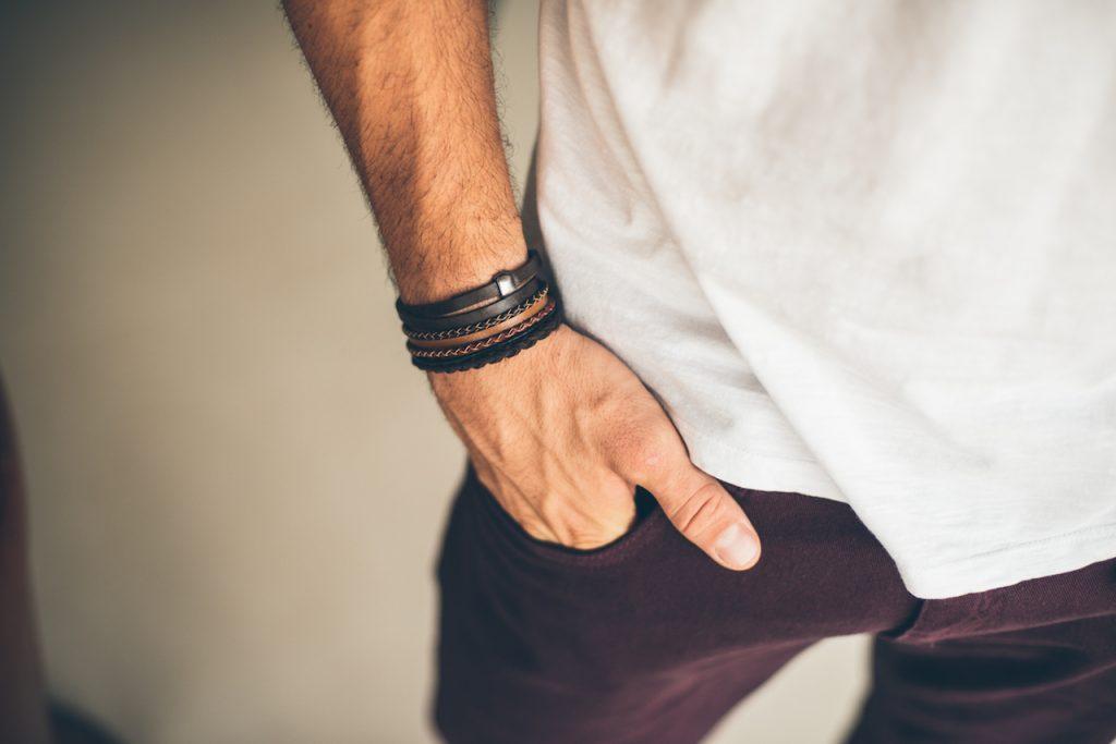 homem usando pulseiras de couro